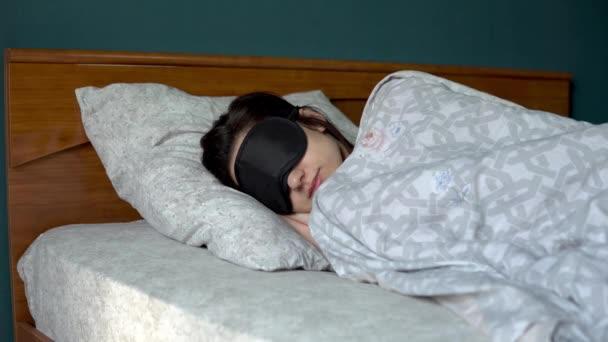 Egy fiatal nő álarcban alszik. Egy lány fekszik az ágyban a szobájában..