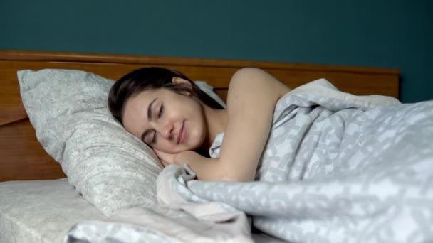 Egy fiatal nő alszik a takaró alatt. Egy lány fekszik az ágyban a szobájában..
