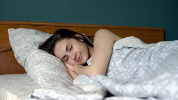 A fiatal nő felébredt. A nő az ágyon aludt a szobájában..