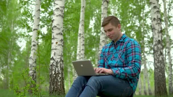 Fiatal ember a természetben, laptoppal a kezében. Egy férfi ül egy fatönkön egy nyírfa erdőben, és vezeti a munkákat egy netbook-on keresztül..