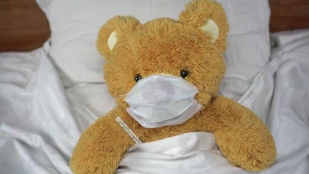 Ein Teddybär misst die Temperatur mit einem Quecksilberthermometer. Der Bär liegt mit einer medizinischen Maske im Bett.