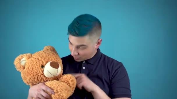 Ein junger Mann mit blauen Haaren hält einen Teddybär in der Hand. Alternativer Mann wedelt mit der Hand und blickt in die Kamera auf blauem Hintergrund.
