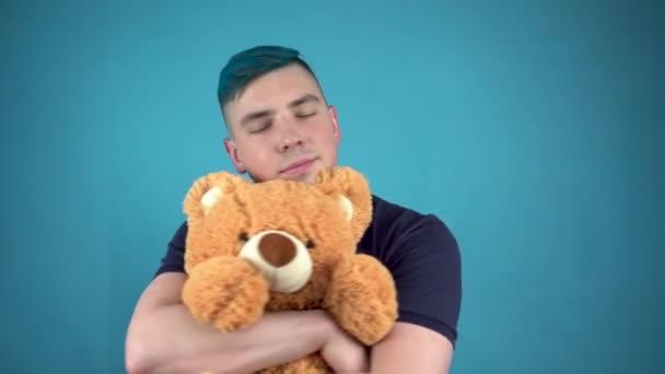 Ein junger Mann mit blauen Haaren hält einen Teddybär in der Hand. Alternativer Mann umarmt ein Stofftier auf blauem Hintergrund.