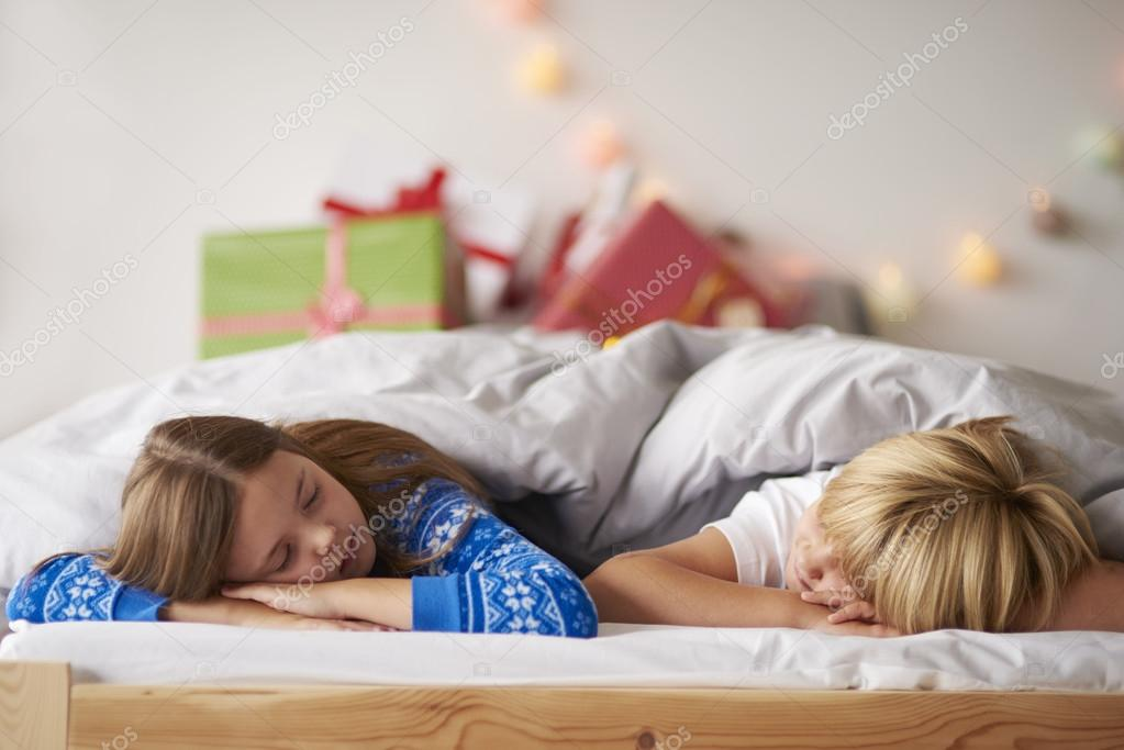 Kids sleeping in comfortable bed at Christmas