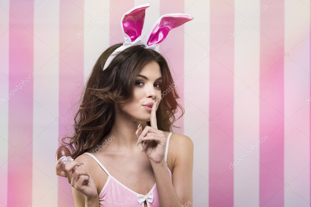 Sexy female rabbit on pink and white background