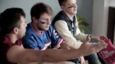 Sad young adults watching football game