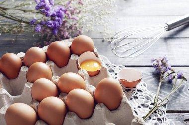 Broken egg among eggs in egg box stock vector