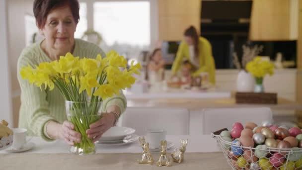 Fröhliche Oma arrangiert Blumen in der Küche