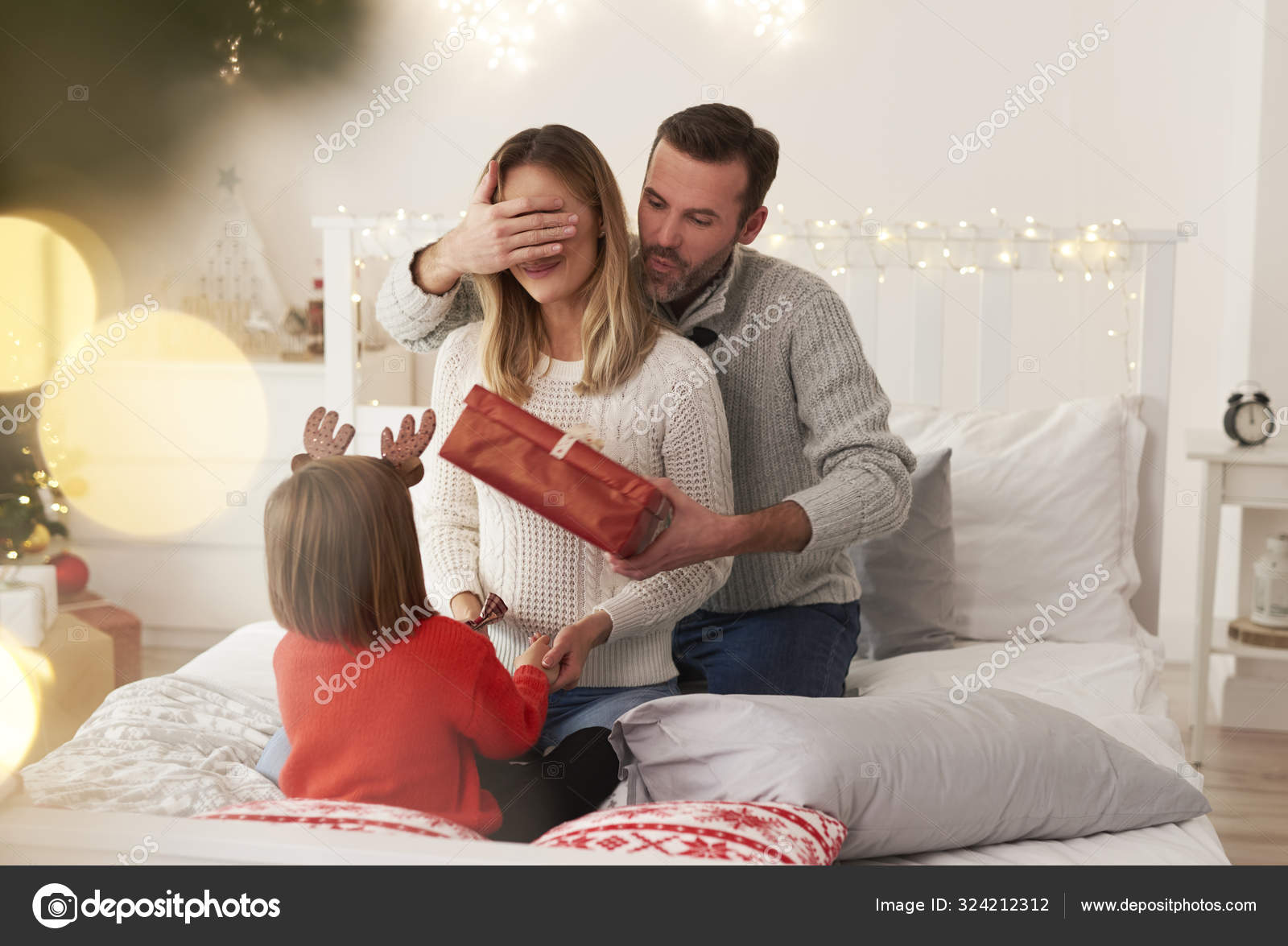 Family starting Christmas from opening presents in bed