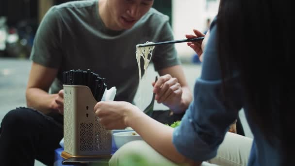 Kézi nézet a vietnami ételeket kipróbáló párról. Vörös hélium kamerával 8k-ban.