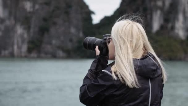 Ruční pohled na turisty s fotoaparátem fotografování mořského pláště. Snímek s RED heliovou kamerou v 8K