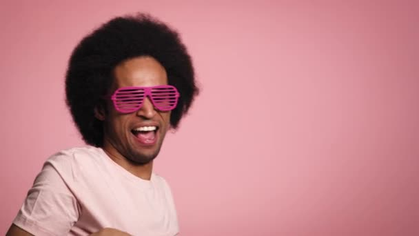 Young African man smiling and dancing in the pink glasses. Shot with RED helium camera in 8K.