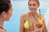 Schöne junge Frauen genießen ihren gemeinsamen Sommerurlaub
