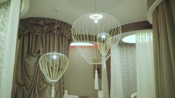 Bird cage-shaped lamps hanging in a rest room lined with curtains and tulles