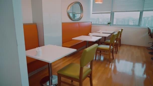 Üres világos kávézó asztalokkal székek és nagy ablakok és világos soffits a mennyezeten
