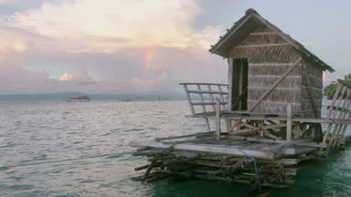 Indonesia. Evening on the shore of a tropical island. Amazing clouds and a piece of rainbow. Hut on the raft in the foreground