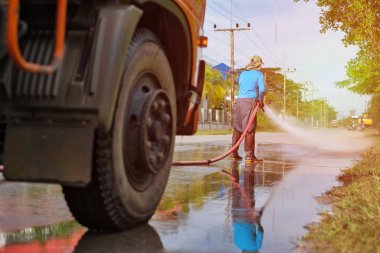 a worker spraying water to clean the road with pressurized water system, wet cleaning of street. with sun light