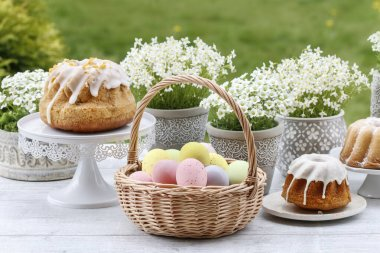 Wicker basket with Easter eggs in the garden.