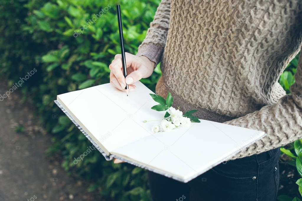 Landscape designer /  architect woman is making notes and is drawing sketches for new project