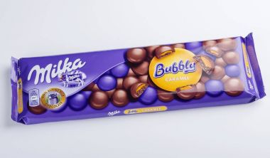 Bar of Milka chocolate isolated on white.  Milka is a brand of chocolate confection which originated in Switzerland in 1901.