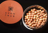 KWIDZYN, POLAND  MARCH 1, 2018: Avon glow bronzing pearls isolated on dark background. Avon Products Inc was founded by David McConnell in 1886 in England. Avon is direct selling company in beauty, household and personal care categories.