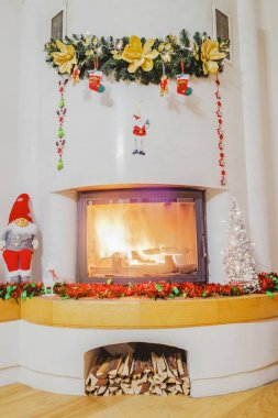 Christmas decorations in living room with burning fireplace
