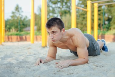 Man is making a plank during workout. Outdoor gym background