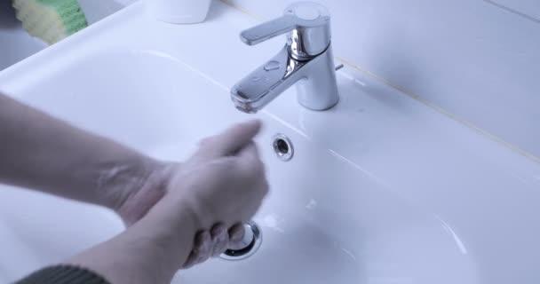 Férfi kezet mos otthon a fürdőszobában. COVID-19 világjárvány 2020-ban