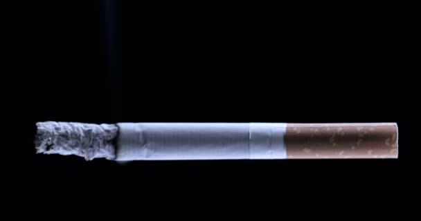 Parázsló cigaretta fekete háttérrel. Füst a cigarettából