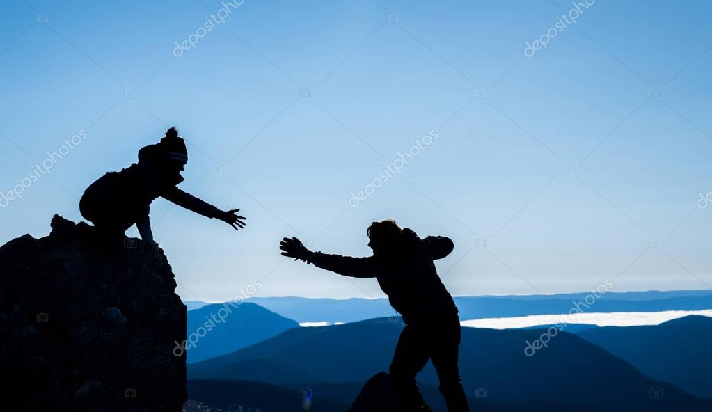 Couple in silhouettes helping each other for Sucess