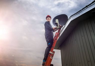 Cheerful young man standing on ladder and mounting residential satellite on roof.