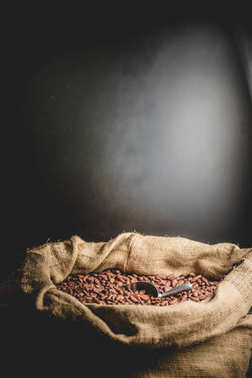 Canvas bag with delicious roasted cacao beans on black background.