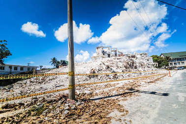 SAN ANDRES ISLAND, Colombia - Circa March 2017: Destroyed Concrete Building near The Airport of San Andres with Employees Working at Cleaning the Zone.