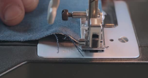 Close-Up Mans Hand Sewing With Denim Jeans On A Sewing Machine. Alteration Jeans, Hemming A Pair Of Jeans, Handmade Garment Industrial Concept. Cinema 4k Video. C4K