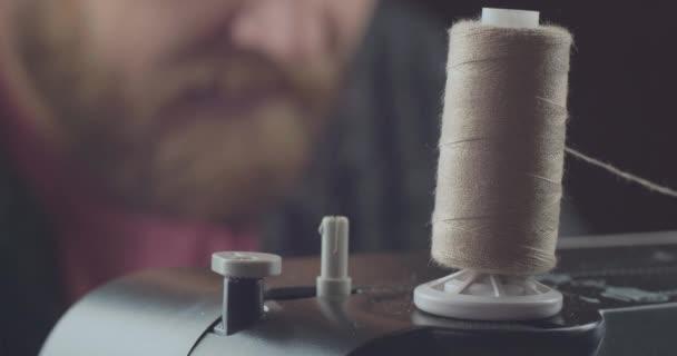 closeup skein of gray thread on a working professional sewing machine on a blurred background craftmaster. unwind the thread. skeins of thread. cinema 4k video. C4K