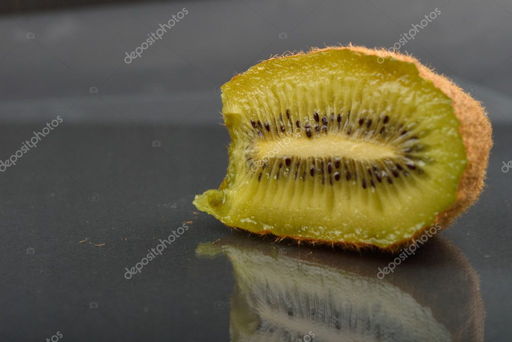 Close up of a half of kiwi which was bitten with teeth with wize
