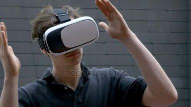 Mladý muž pomocí Vr Headset dělá gesta rukou