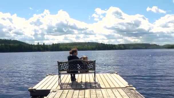 Matka a dítě sedí u jezera