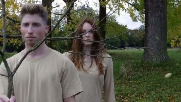 Portrét muže a ženy držící holé větve