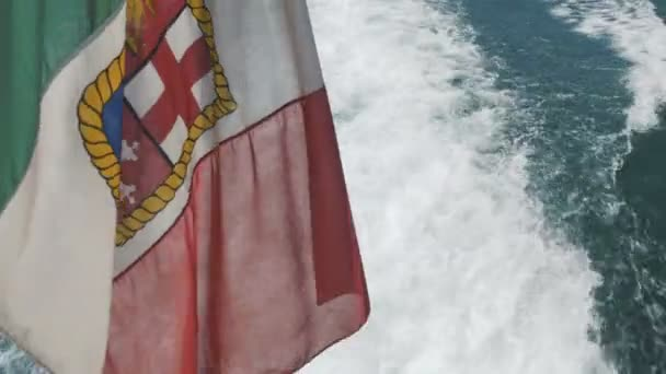 The Ensign Flag of Italy Above the Trail of a Motorboat in the Waters of Lake Garda