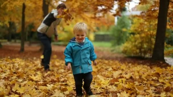 Childhood Moments: Teenager and Little Boy Playing With Autumn Leaves in Park