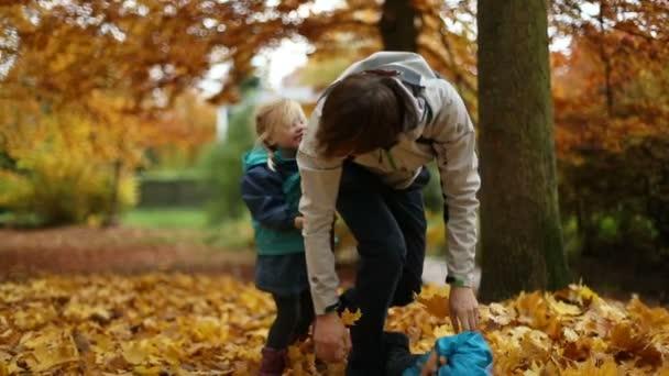 Okamžiky dětství: Dospívající a děti si hrají s podzimní listí v parku 2