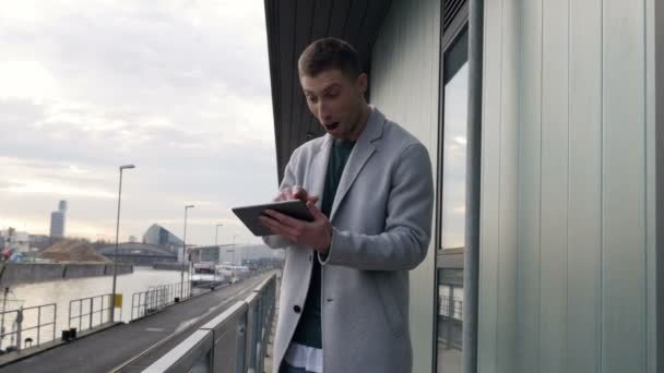 aufgeregter junger Mann mit Tablet im Freien