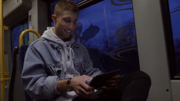 Smiling Young Man Using Tablet in Tram