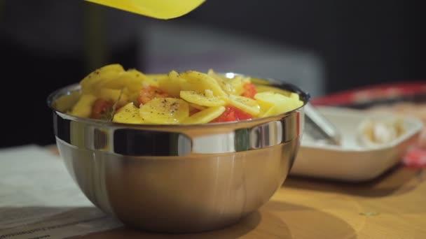 Slow Motion vaření: Nasekané petrželky do misky plátky syrových brambor v kastrolu