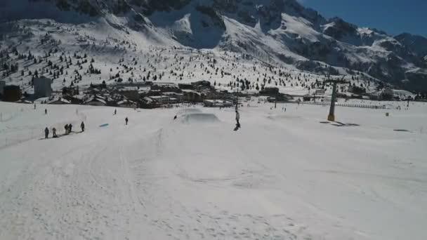 Snowboarder springt von einem Hügel mit Berggipfeln im Vordergrund