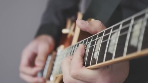 Fingers on guitar fretboard playing rock, jazz and blues solo. Close up hands playing electric guitar. Guitar practice for rock concert