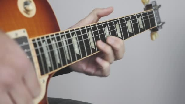 Kytarista hraje sólo na elektrickou kytaru. Rock sólo na kytaru hudební nástroje zblízka. Fretboard a headstock elektrické kytary
