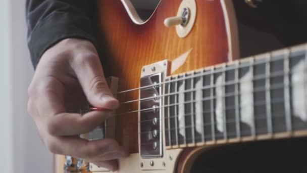 Muž ruka s krumpáčem hrát na elektrickou kytaru vybírání a brnkání. Mužská ruka a kytara struny s pickupy hrát rockovou píseň. Hudební koncept