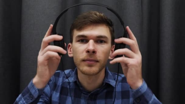 Portrait of man listening to music in headphones. Young smiling male putting on headphones and listening song on grey background